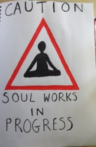 a road works sign but with sillohet of someone meditation, captioon read Caution Soul Works in Progress