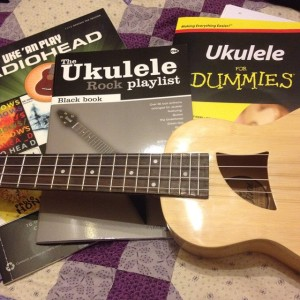 Ukulele music books and ukulele on a purple patchwork quilt